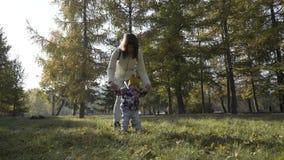 Μεγάλες καθιερώνουσες τη μόδα νέες μητέρες που περπατούν στο πάρκο με τις κόρες του στον όμορφο ιματισμό απόθεμα βίντεο