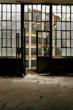 Μεγάλες παράθυρα & πόρτα που κοιτάζουν έξω - εγκαταλειμμένο ντύνοντας εργοστάσιο στοκ φωτογραφία