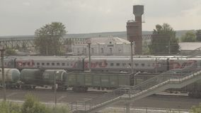 Μεγάλης απόστασης επιβατική αμαξοστοιχία και φορτηγό τρένο στο μικρό σταθμό Uzunovo RZD απόθεμα βίντεο
