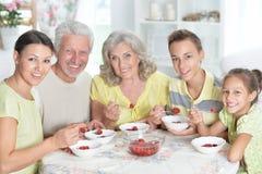 Μεγάλη ευτυχής οικογένεια που τρώει τις φρέσκες φράουλες στην κουζίνα Στοκ Εικόνα