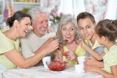Μεγάλη ευτυχής οικογένεια που τρώει τις φρέσκες φράουλες στην κουζίνα Στοκ Εικόνες