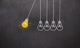 μεγάλη ιδέα Έννοια δημιουργικότητας με τις λάμπες φωτός στον πίνακα κιμωλίας στοκ φωτογραφία