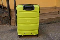 Μεγάλη κίτρινη πλαστική βαλίτσα στο πεζοδρόμιο κοντά στον τοίχο και βήματα στην οδό Στοκ Εικόνα