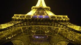 Μεγάλη κατασκευή του πύργου του Άιφελ που φωτίζεται με πολλά φωτεινά φω'τα σπινθηρίσματος απόθεμα βίντεο