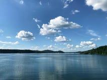 Μεγάλη λίμνη στα ευρωπαϊκά βουνά Solina, Πολωνία Μεγάλο, χνουδωτό επιπλέον σώμα σύννεφων πέρα από το μπλε ουρανό στοκ εικόνα