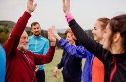 Μεγάλη ομάδα κατάλληλων και ενεργών ανθρώπων που στηρίζονται μετά από να κάνει την άσκηση στη φύση στοκ εικόνες