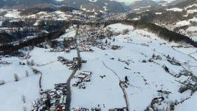 Μεγάλη πόλη που καλύπτεται στο χιόνι με ένα ογκώδες βουνό κοντά σε το, εναέριος πυροβολισμός, 4k απόθεμα βίντεο