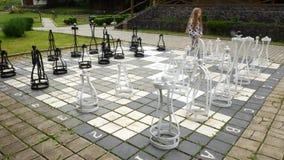 Μεγάλη σκακιέρα στο ναυπηγείο Το παιδί ρυθμίζει εκ νέου τα βαριά κομμάτια σκακιού απόθεμα βίντεο