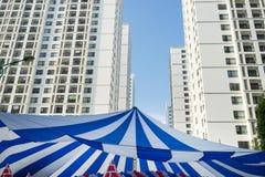 Μεγάλη στέγη σκηνών καμβά ενάντια στις πολυκατοικίες και μπλε ουρανός στο υπόβαθρο Έννοια των υπαίθριων δραστηριοτήτων εορτασμού  Στοκ Φωτογραφίες