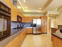 Μεγάλη σύγχρονη ξύλινη κουζίνα με το καθιστικό και το υψηλό ανώτατο όριο. Στοκ Φωτογραφίες