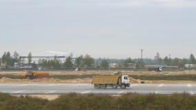 Μεγάλοι γύροι φορτηγών στο δρόμο Το φορτηγό μεταφέρει το υλικό Κατασκευή, των διαδρόμων αερολιμένων, δρόμοι tippers απόθεμα βίντεο