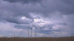 Μεγάλοι ηλεκτρικοί πυλώνες ενάντια στον ουρανό με τα συμπαθητικά thunderclouds