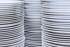 Μεγάλοι σωροί των καθαρών άσπρων πιάτων μετά από την πλύση στην κουζίνα στοκ εικόνα με δικαίωμα ελεύθερης χρήσης