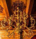 Μεγάλοι όμορφοι πολυέλαιοι, χρυσό χρώμα, υψηλοί όμορφοι πολυέλαιοι που κρεμούν από το ανώτατο όριο το σχέδιο ντεκόρ ανασκόπησης δ Στοκ Φωτογραφία