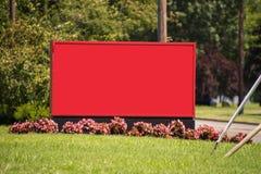 Μεγάλος κενός κόκκινος πίνακας σημαδιών στην πράσινη χλόη με τα μικρά λουλούδια στη βάση και το θολωμένο έξω υπόβαθρο δέντρων του στοκ φωτογραφία
