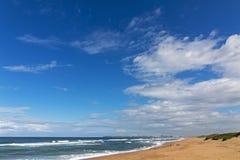 Μεγάλος μπλε νεφελώδης ουρανός και απόμακρος παράκτιος ορίζοντας πόλεων στοκ εικόνες