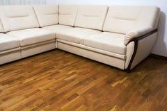 Μεγάλος νέος μπεζ καναπές στο ξύλινο πάτωμα παρκέ στοκ φωτογραφίες με δικαίωμα ελεύθερης χρήσης
