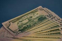 Μεγάλος παχύς ρόλος χρημάτων σε ένα μπλε υπόβαθρο στοκ εικόνες