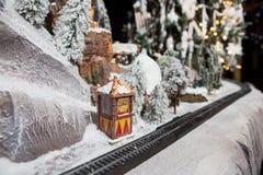 Μεγάλος σιδηρόδρομος παιδιών ` s διακοσμήσεων ασβεστοκονιάματος διακοσμήσεων Χριστουγέννων στις χειμερινές χιονισμένες ράγες στα  Στοκ Φωτογραφίες
