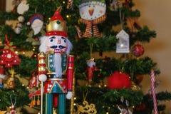 Μεγάλος στρατιώτης καρυοθραύστης κασσίτερου σε ένα χριστουγεννιάτικο δέντρο με το θολωμένο υπόβαθρο στοκ εικόνα