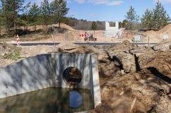 Μεγάλος συγκεκριμένος νέος συλλέκτης για το νερό υπονόμων και τους σωρούς της άμμου με τα ίχνη βαριών ροδών εξοπλισμού σε ένα εργ στοκ εικόνες