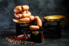 Μεγάλος σωρός των παχιών κοντών λουκάνικων στη σπείρα με το κρεμμύδι και το τσίλι στοκ φωτογραφίες
