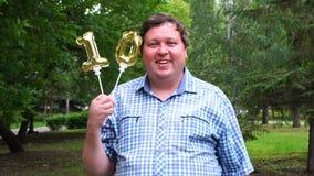 Μεγάλο άτομο που κρατά δύο χρυσά μπαλόνια που κάνουν 10 αριθμός τον υπαίθριο 10ο κόμμα εορτασμού επετείου απόθεμα βίντεο