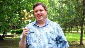 Μεγάλο άτομο που κρατά τα χρυσά μπαλόνια που κάνουν 14 αριθμός τον υπαίθριο 14ο κόμμα εορτασμού επετείου απόθεμα βίντεο