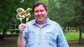 Μεγάλο άτομο που κρατά τα χρυσά μπαλόνια που κάνουν 24 αριθμός τον υπαίθριο 24ο κόμμα εορτασμού επετείου απόθεμα βίντεο