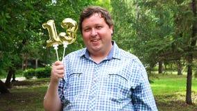 Μεγάλο άτομο που κρατά τα χρυσά μπαλόνια που κάνουν 13 αριθμός τον υπαίθριο 13ο κόμμα εορτασμού επετείου απόθεμα βίντεο