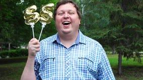 Μεγάλο άτομο που κρατά τα χρυσά μπαλόνια που κάνουν 55 αριθμός τον υπαίθριο 55ο κόμμα εορτασμού επετείου φιλμ μικρού μήκους