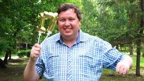 Μεγάλο άτομο που κρατά τα χρυσά μπαλόνια που κάνουν 17 αριθμός τον υπαίθριο 17ο κόμμα εορτασμού επετείου απόθεμα βίντεο
