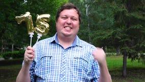Μεγάλο άτομο που κρατά τα χρυσά μπαλόνια που κάνουν 75 αριθμός τον υπαίθριο 75ο κόμμα εορτασμού επετείου φιλμ μικρού μήκους