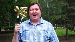 Μεγάλο άτομο που κρατά τα χρυσά μπαλόνια που κάνουν 95 αριθμός τον υπαίθριο 95ο κόμμα εορτασμού επετείου απόθεμα βίντεο