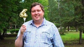 Μεγάλο άτομο που κρατά το χρυσό μπαλόνι που κάνει 4 αριθμός τον υπαίθριο 4ο κόμμα εορτασμού επετείου απόθεμα βίντεο