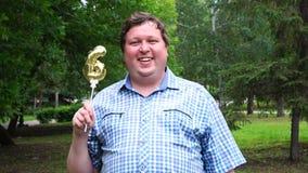 Μεγάλο άτομο που κρατά το χρυσό μπαλόνι που κάνει 6 αριθμός τον υπαίθριο 6ο κόμμα εορτασμού επετείου φιλμ μικρού μήκους