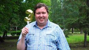 Μεγάλο άτομο που κρατά το χρυσό μπαλόνι που κάνει 3 αριθμός τον υπαίθριο 3ο κόμμα εορτασμού επετείου απόθεμα βίντεο