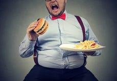 Μεγάλο άτομο στα επίσημα ενδύματα που κάθονται και που καταναλώνουν το πιάτο με το γρήγορο φαγητό στοκ φωτογραφία