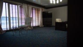 Μεγάλο δωμάτιο με τα μεγάλα παράθυρα, τους πίνακες και τις πολυθρόνες και τον μπλε τάπητα Σύγχρονη άποψη δωματίου ξενοδοχείου απόθεμα βίντεο