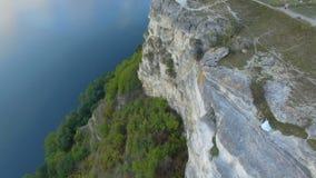 Μεγάλο ηλιοβασίλεμα στη λίμνη μεταξύ των βουνών Ένα ζεύγος που αγκαλιάζει στην άκρη του απότομου βράχου 4K φιλμ μικρού μήκους
