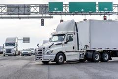 Μεγάλο ημι φορτηγό αμαξιών ημέρας εγκαταστάσεων γεώτρησης με το ημι ρυμουλκό που ανοίγει τη διατομή σταυροδρομιών με τους φωτεινο στοκ εικόνες