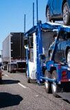 Μεγάλο ημι φορτηγό εγκαταστάσεων γεώτρησης με το ρυμουλκό μεταφορέων αυτοκινήτων που μεταφέρει τα αυτοκίνητα επάνω Στοκ φωτογραφία με δικαίωμα ελεύθερης χρήσης