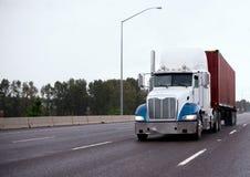 Μεγάλο ημι φορτηγό εγκαταστάσεων γεώτρησης που μεταφέρει το εμπορευματοκιβώτιο στο ευθύ ευρύ highw Στοκ Φωτογραφία