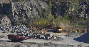 Μεγάλο κίτρινο φορτηγό απορρίψεων σε ένα λατομείο φορτηγών λατομείων, εκσκαφέων και απορρίψεων, βιομηχανικό φορτηγό απορρίψεων σε απόθεμα βίντεο