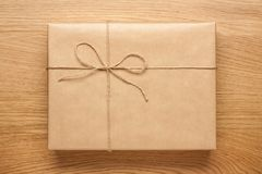 Μεγάλο κιβώτιο δώρων που τυλίγεται στο έγγραφο του Κραφτ για τον ξύλινο πίνακα στοκ εικόνες