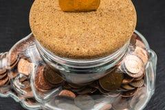 Μεγάλο κιβώτιο χρημάτων τράπεζας Piggy, βάζο χρημάτων γυαλιού με τα βρετανικά νομίσματα στοκ φωτογραφίες