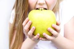 Μεγάλο κιτρινοπράσινο μήλο στα χέρια παιδιών s Κορίτσι που δαγκώνει το μήλο στοκ φωτογραφία με δικαίωμα ελεύθερης χρήσης