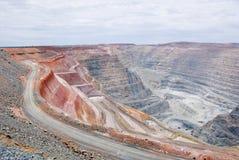 Μεγάλο κοίλωμα ορυχείων με τα truck λίγων απορρίψεων και το κοκκινωπό χώμα Στοκ φωτογραφίες με δικαίωμα ελεύθερης χρήσης