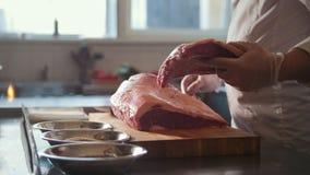 Μεγάλο κομμάτι χασάπηδων prepairs του φρέσκου ακατέργαστου κρέατος που βρίσκεται σε έναν ξύλινο πίνακα σε μια εμπορική κουζίνα φιλμ μικρού μήκους