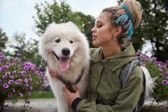 Μεγάλο λεπτομερές οριζόντιο πορτρέτο ενός νέου μοντέρνου κοριτσιού με τα dreadlocks και του λευκού σκυλιού Samoyed της στοκ φωτογραφία με δικαίωμα ελεύθερης χρήσης
